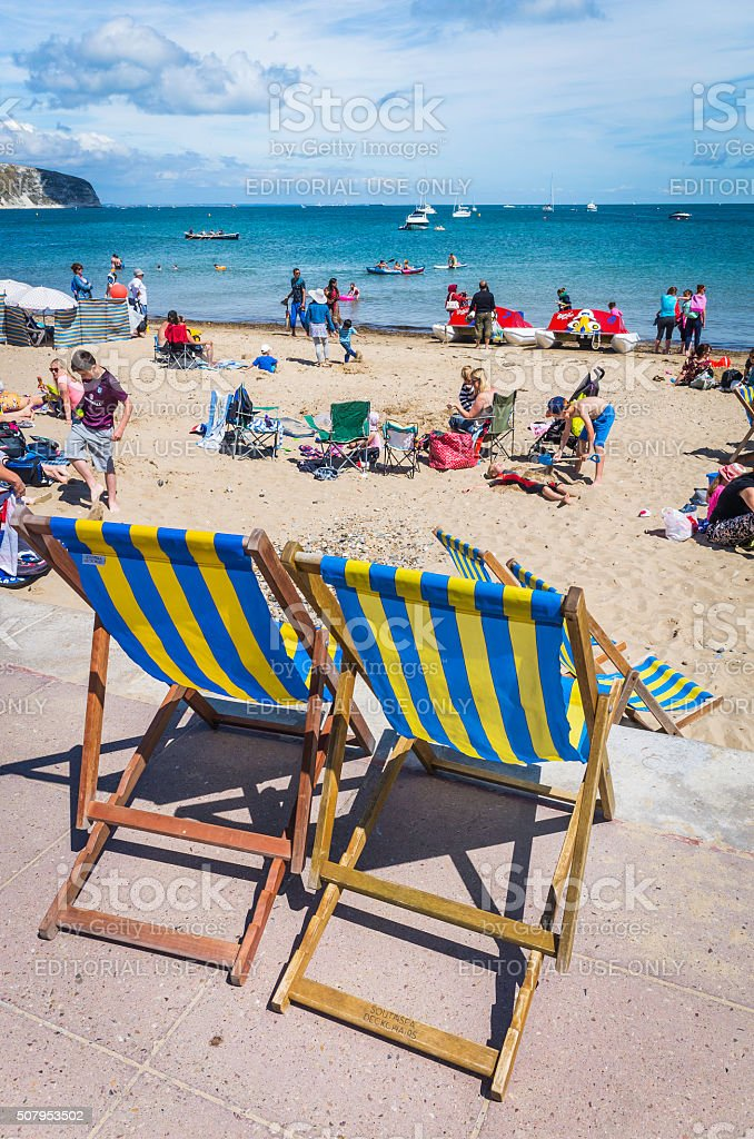 Stripey seaside deckchairs beside a crowded sandy beach holidaymakers sunbathers stock photo