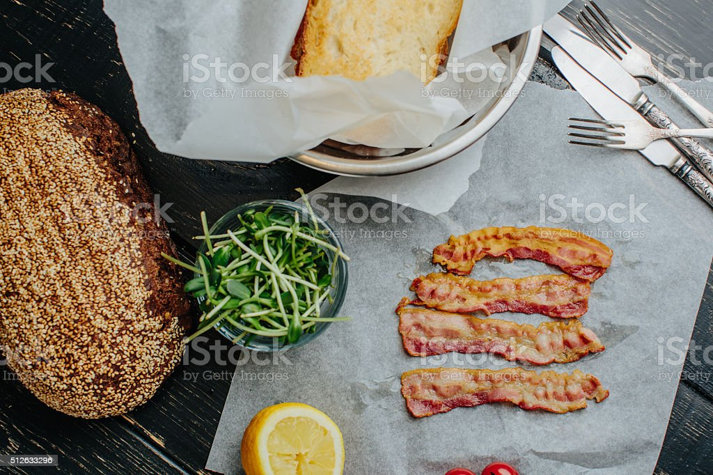 Strips of fried bacon lying on waxed paper stock photo