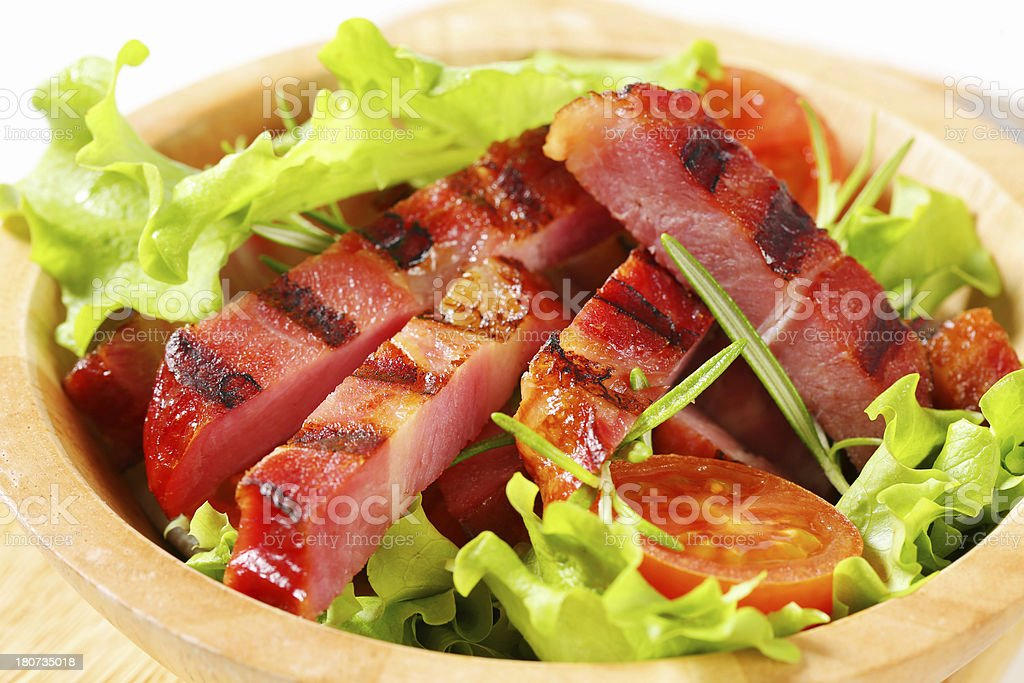 Strips of grilled bacon with vegetable salad in a bowl royalty-free stock photo