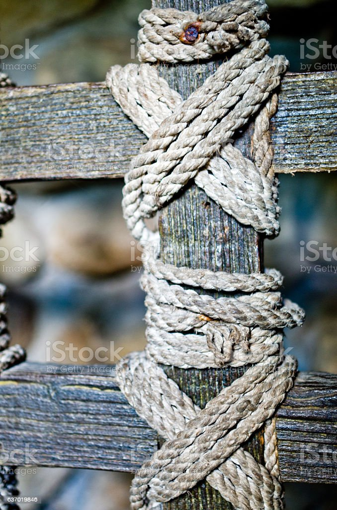 strips of wood held together by an old rope stock photo
