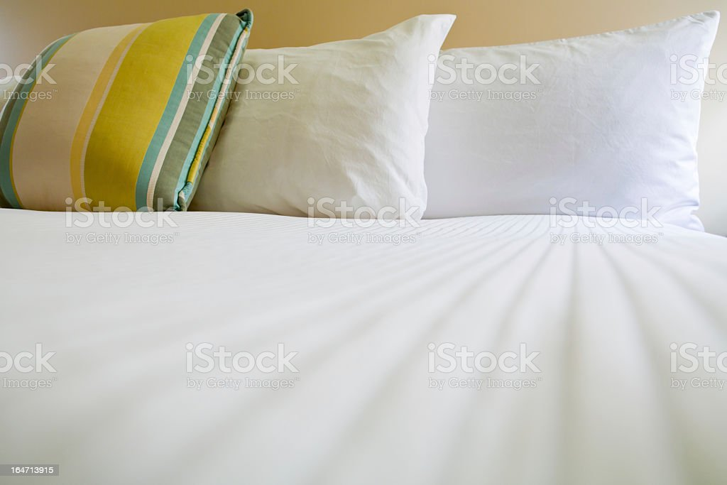 Stripy cushion and two pillows on a double bed stock photo