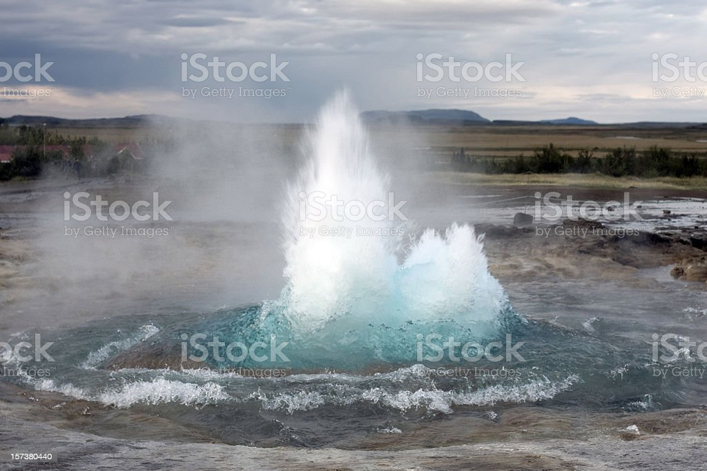 Strokkur Geyser erupts blue water with plains in background stock photo