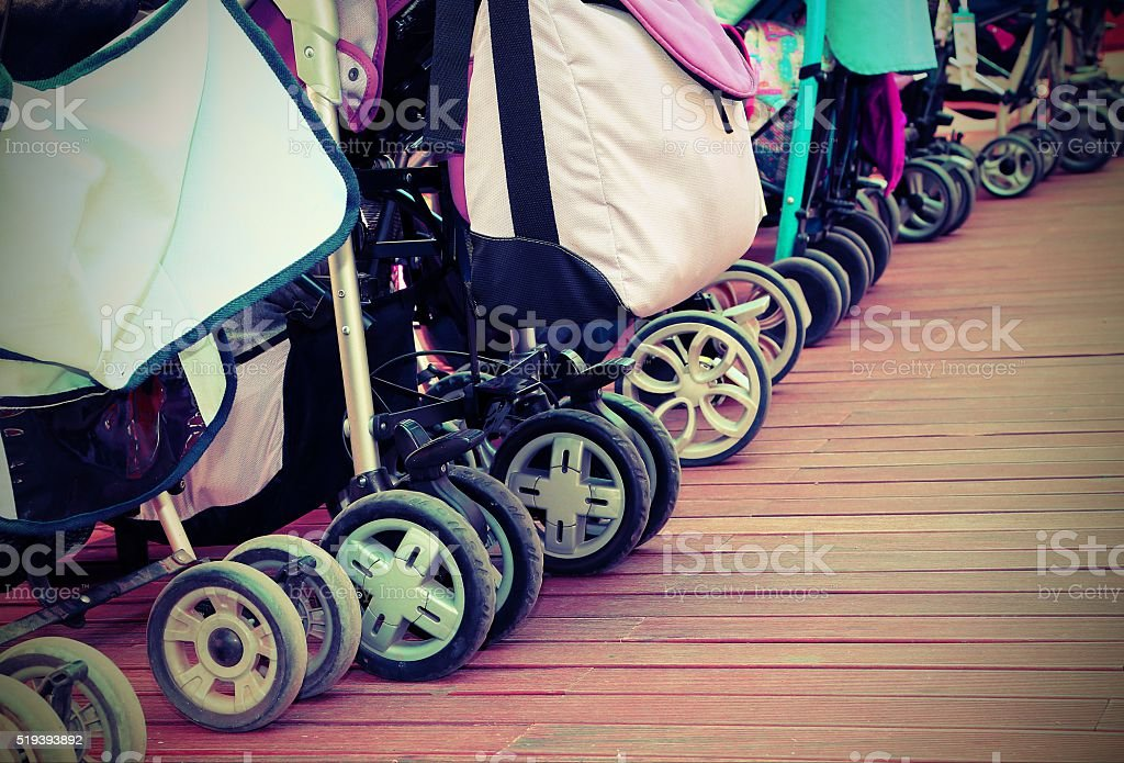 strollers for toddlers parked on the parquet floor of wood stock photo