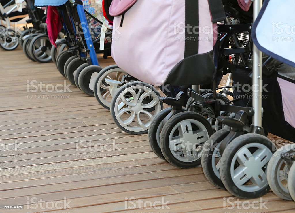 strollers for toddlers parked on the wooden parquet stock photo