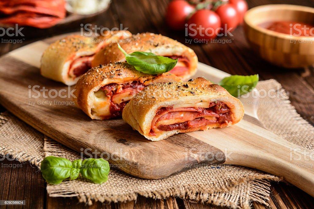 Stromboli stuffed with cheese, salami, green onion and tomato sauce stock photo