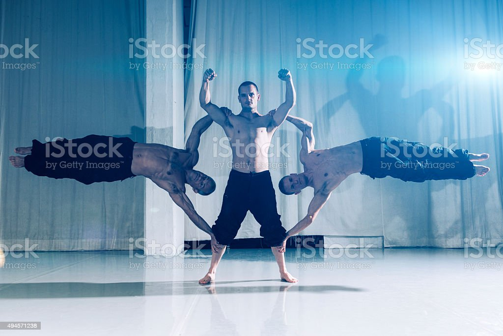 Strong acrobats show of their muscles and strenght stock photo