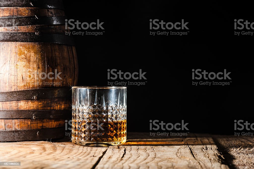 Strong alcohol on a wooden table and barrel stock photo