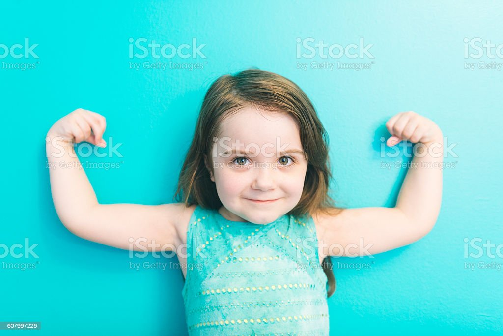 Strong American Girl Looking at Camera Shows Muscles Raising Arms stock photo