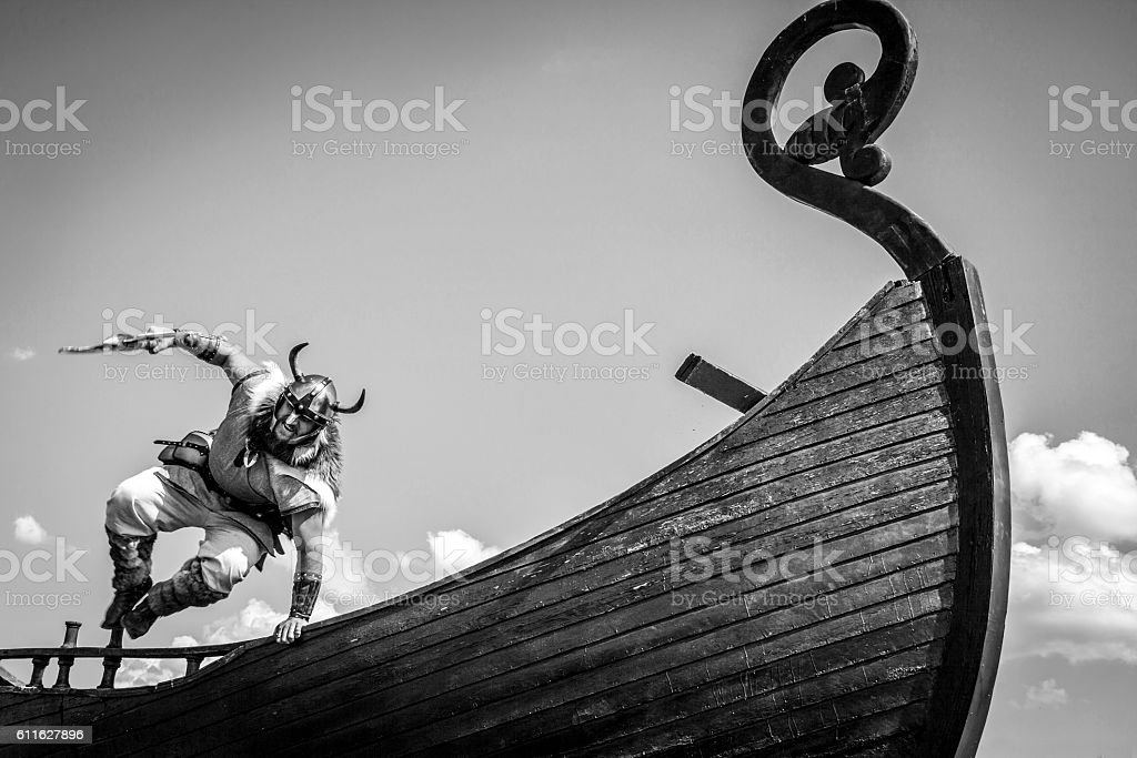 Strong angry bearded Viking with axe attacking. stock photo