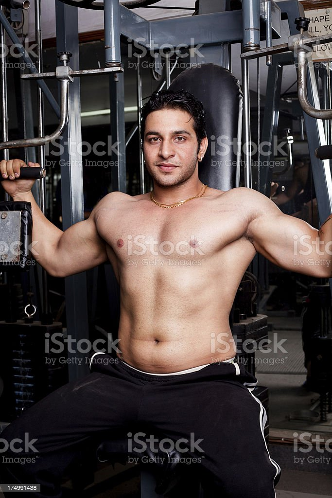 Strong Asian Indian Man Exercising in Gym royalty-free stock photo