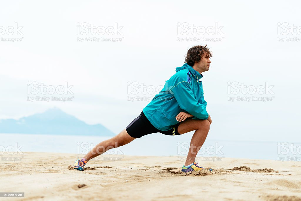 Strong athlete prepares for ironman competition at beach in Greece stock photo