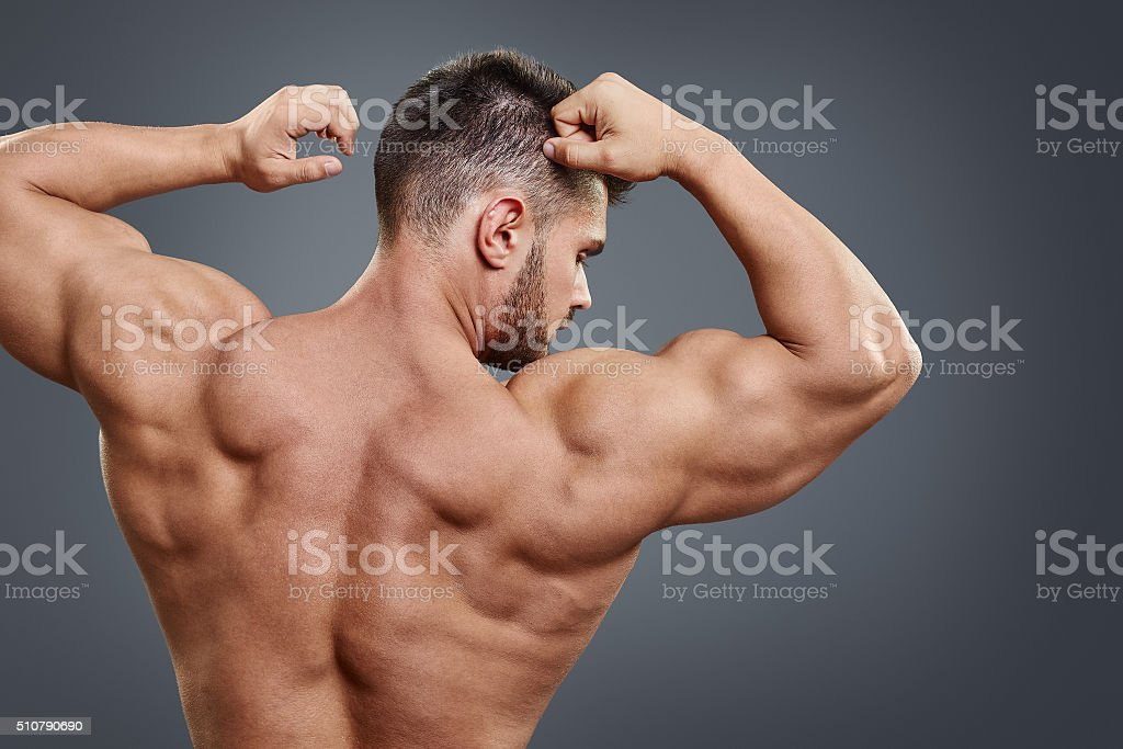 strong athletic man back on grey background stock photo