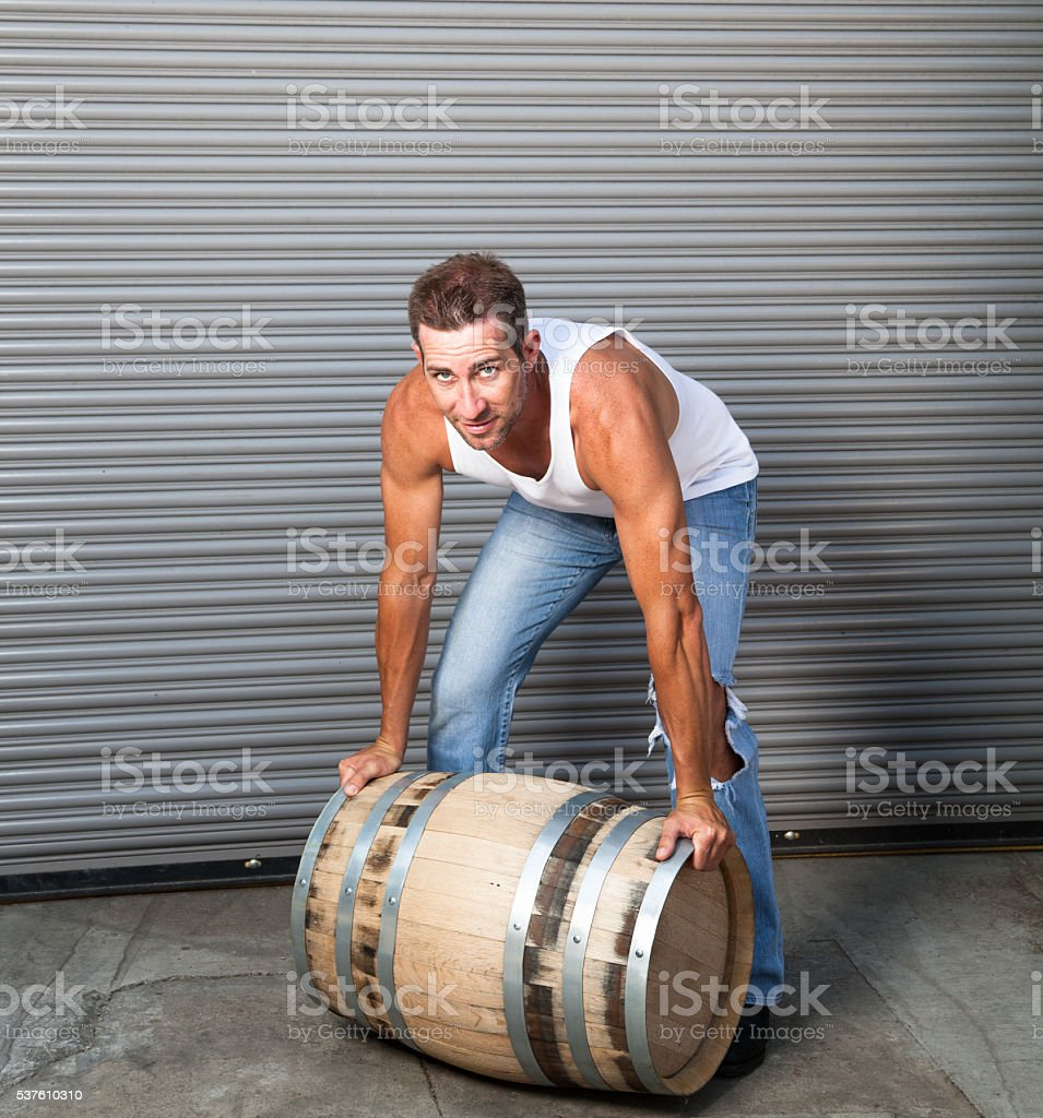 strong athletic man in white shirt by wooden beer barrel stock photo
