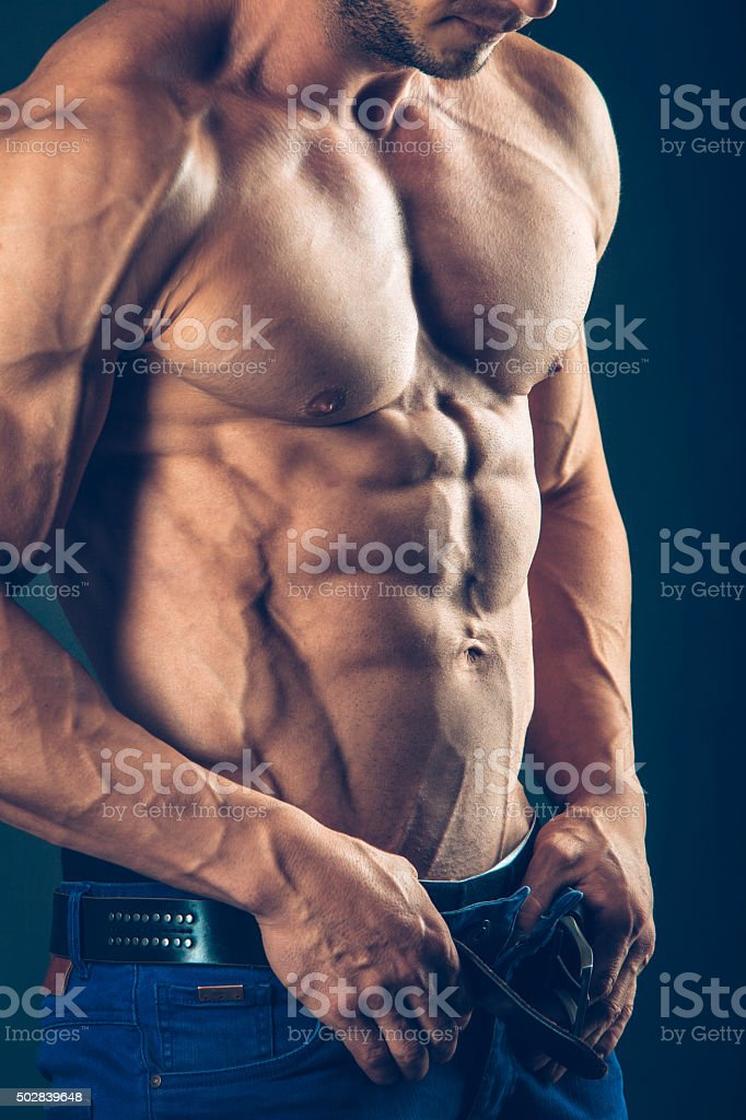 strong athletic man  on black background. To pump the abdominals stock photo