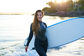 Strong beautiful young woman with surf on the beach