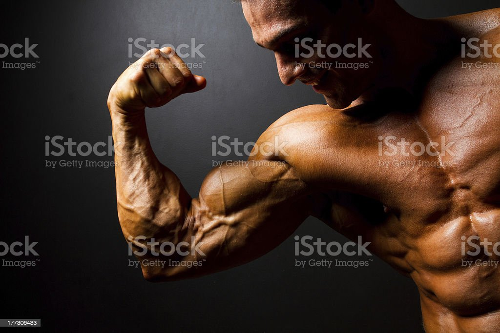 strong bodybuilder posing on black royalty-free stock photo