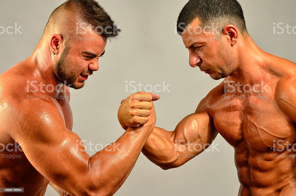 Strong bodybuilders testing their biceps in a skandemberg contest stock photo