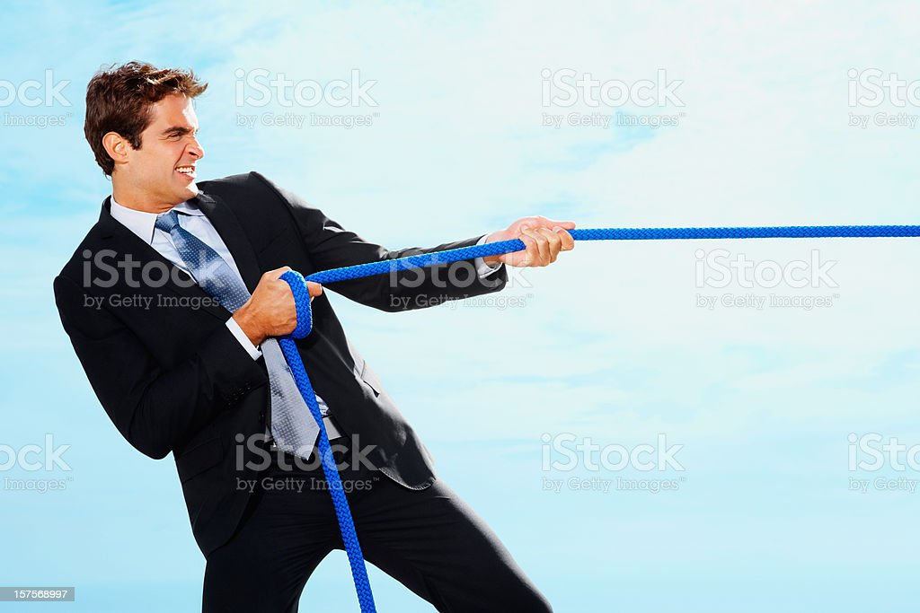 Strong business man pulling a success rope towards his side royalty-free stock photo