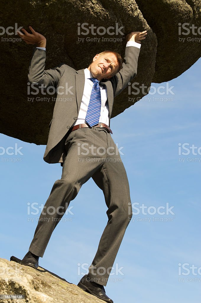 Strong Businessman Holding Up Huge Rock Boulder in the Sky stock photo