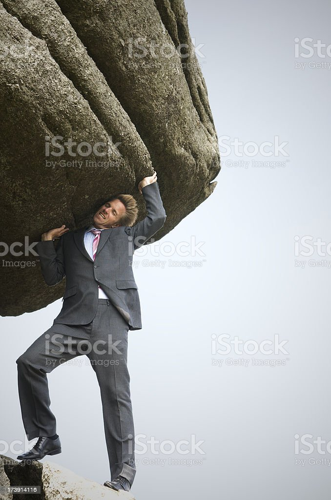 Strong Businessman Struggles to Lift a Big Boulder royalty-free stock photo