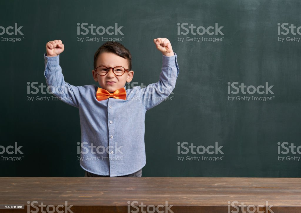 Strong child is in front of chalkboard