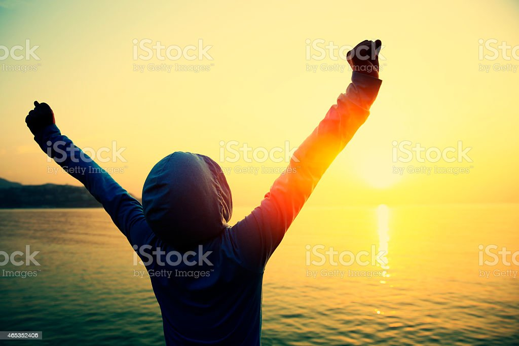 strong confident woman open arms to sunrise at sea stock photo