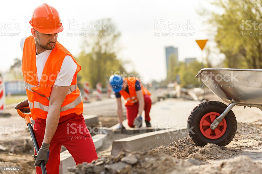 Strong construction worker digging stock photo