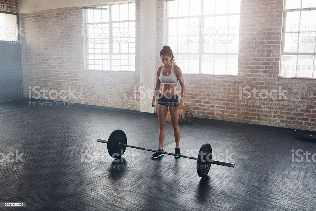 Strong female at gym with barbells stock photo
