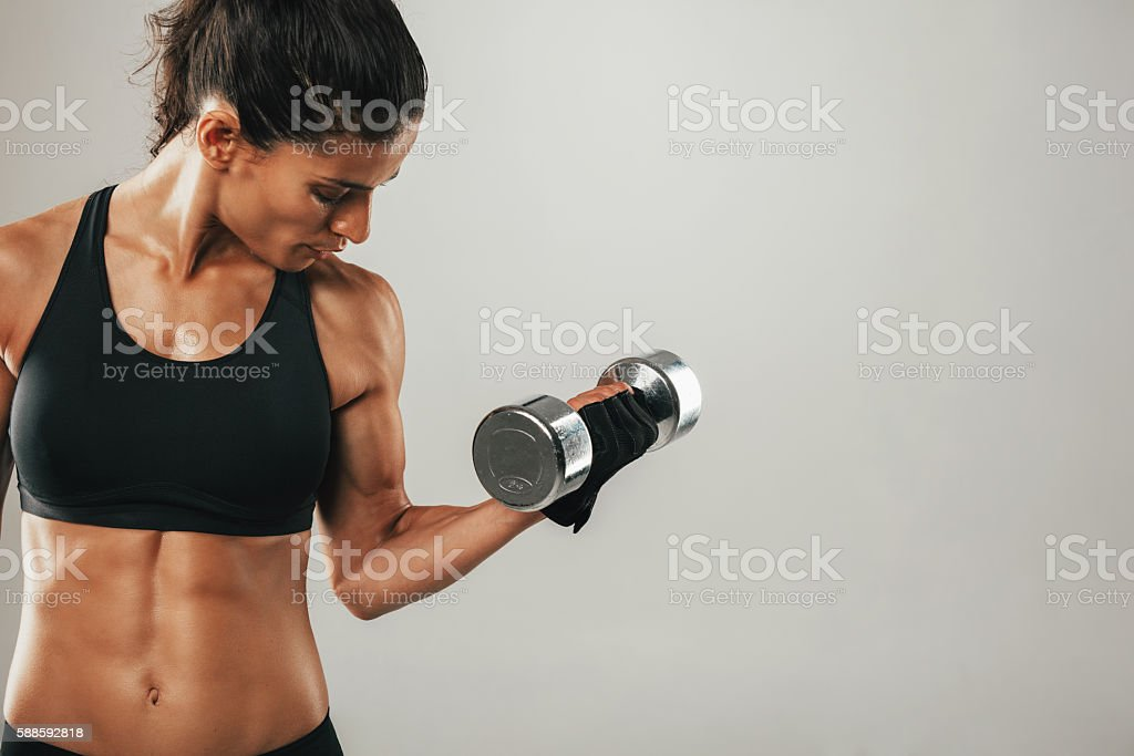 Strong female athlete lifting dumbbell stock photo