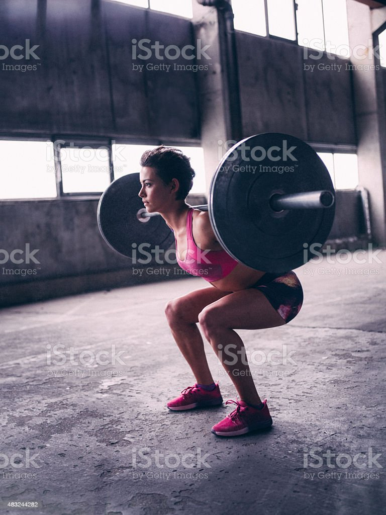 Strong girl with a heavy barbell resting on her shoulders stock photo