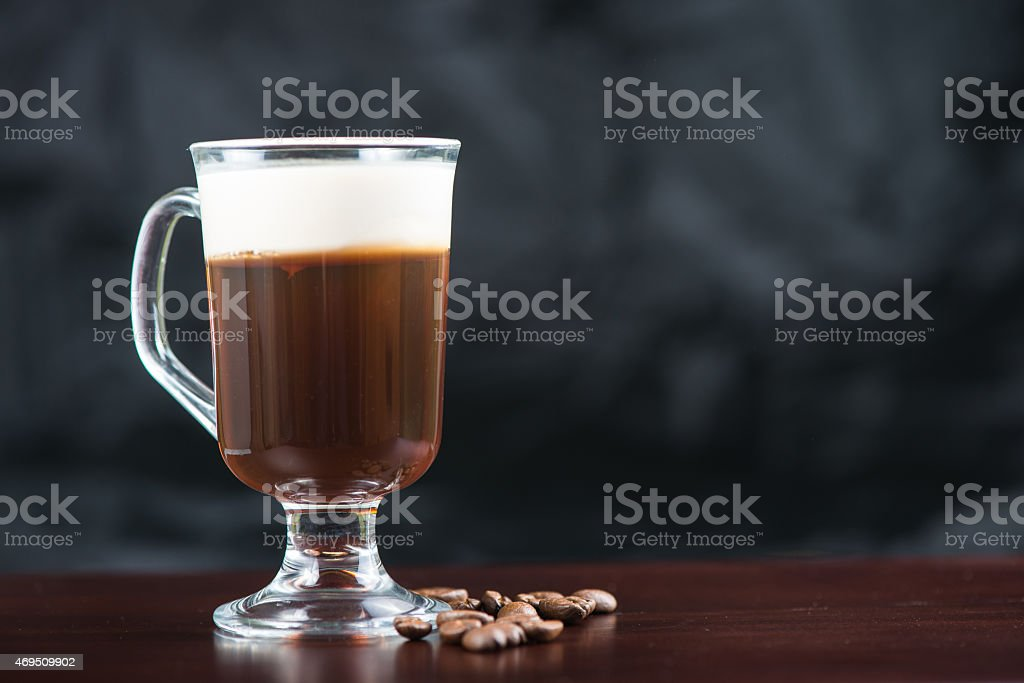 A strong Irish coffee in a glass on top of a wooden bar stock photo