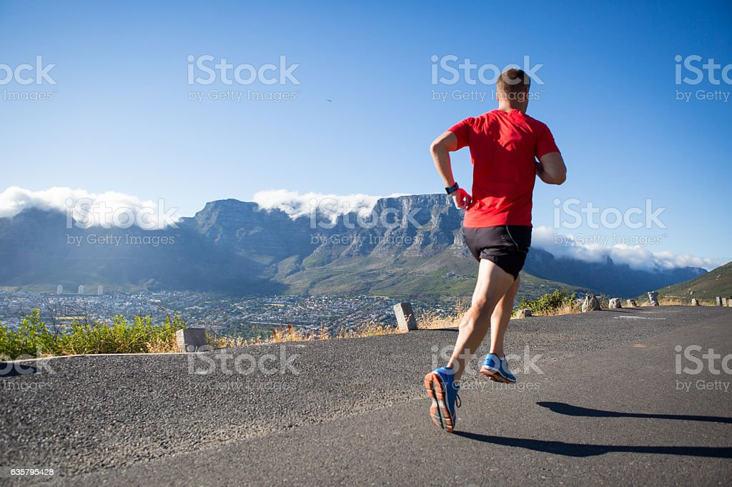 Strong male athlete running on the road stock photo