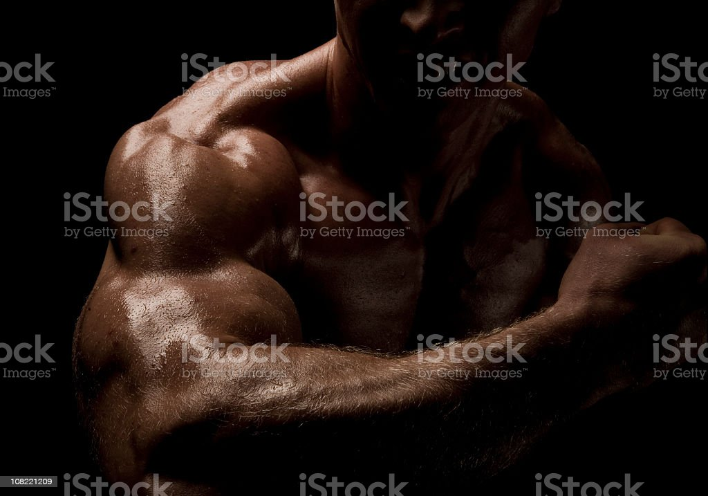 Strong male flexes biceps to reveal muscularity royalty-free stock photo