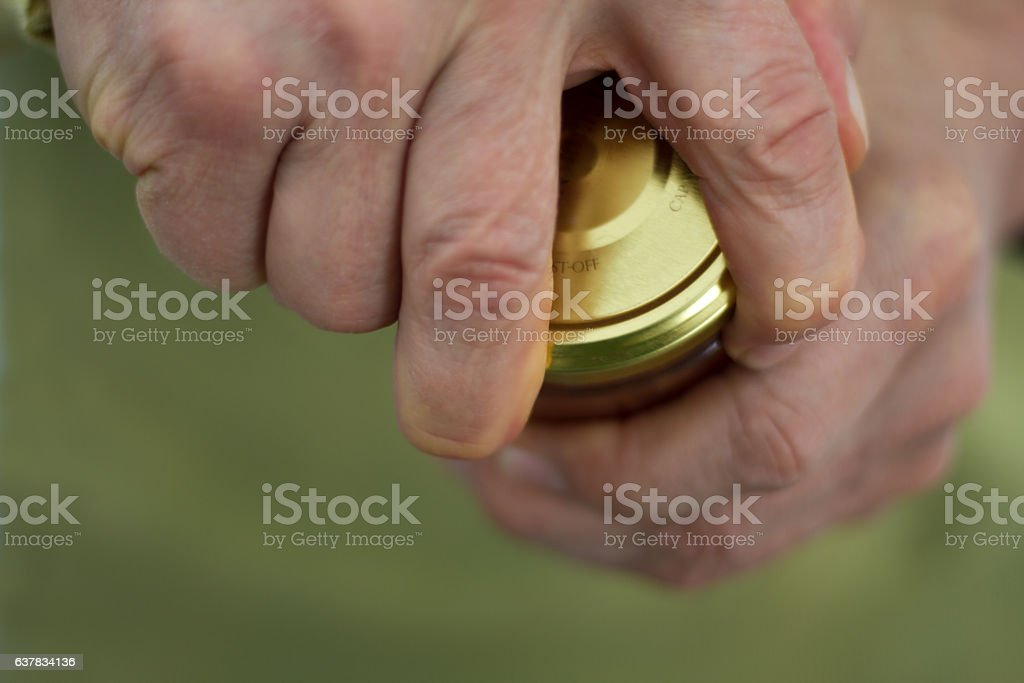 Strong Male Hands Twisting a Stubborn Jar Lid (Close-Up) stock photo