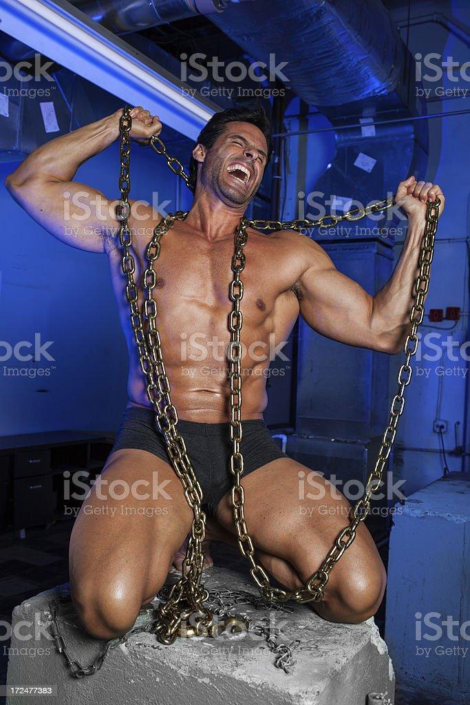 Strong man breaking the chains stock photo