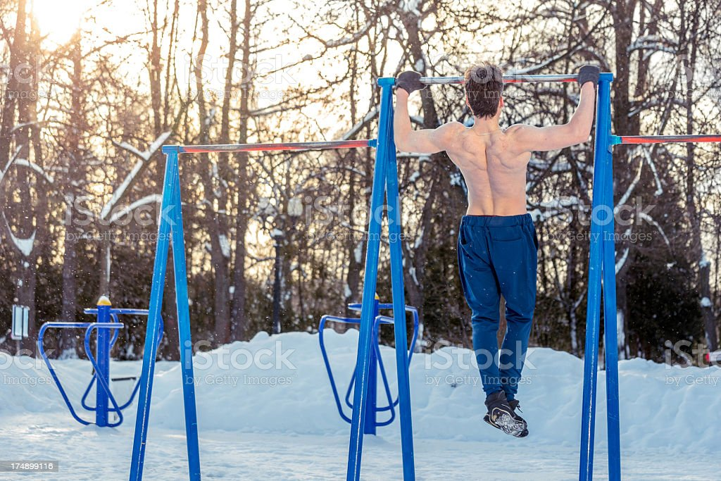 Strong man doing pullups on bar in park royalty-free stock photo