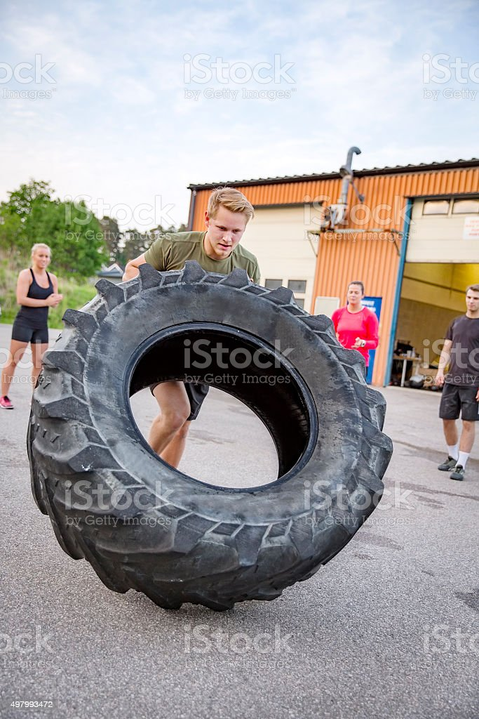 Strong man flips heavy tire outdoor as workout stock photo