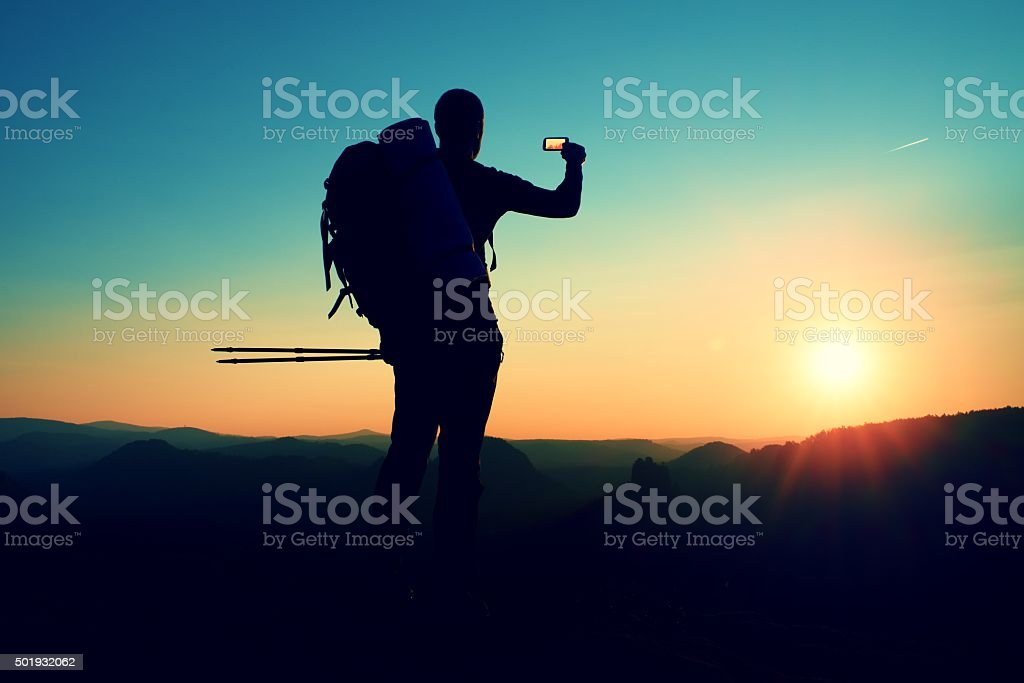 Strong man hiker taking photo with smart phone at mounpeak stock photo