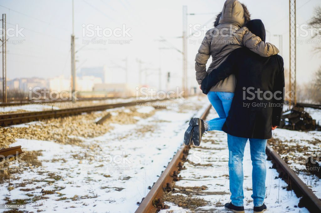 Strong man holding his girlfriend on the railroad stock photo