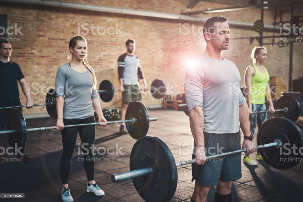 Strong man leading group in barbell exercises stock photo