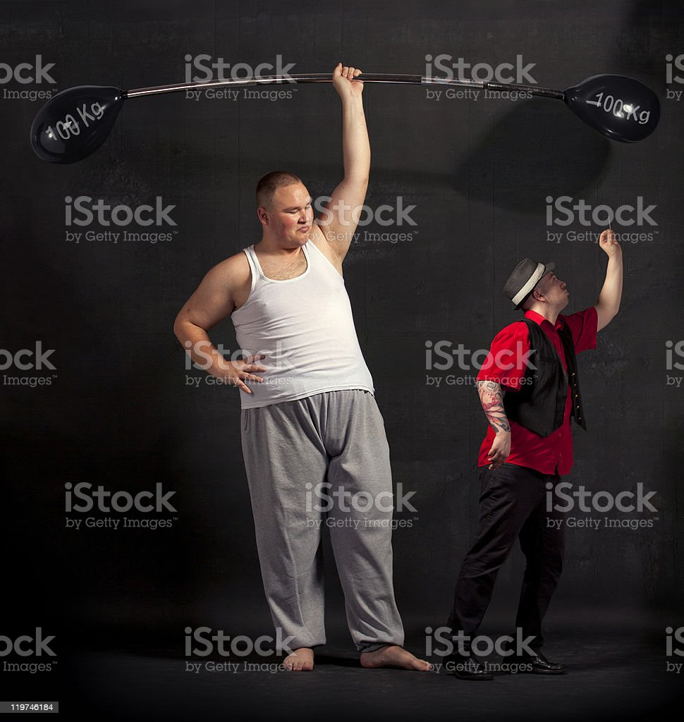 Strong man lifting a balloon barbell on the stage stock photo