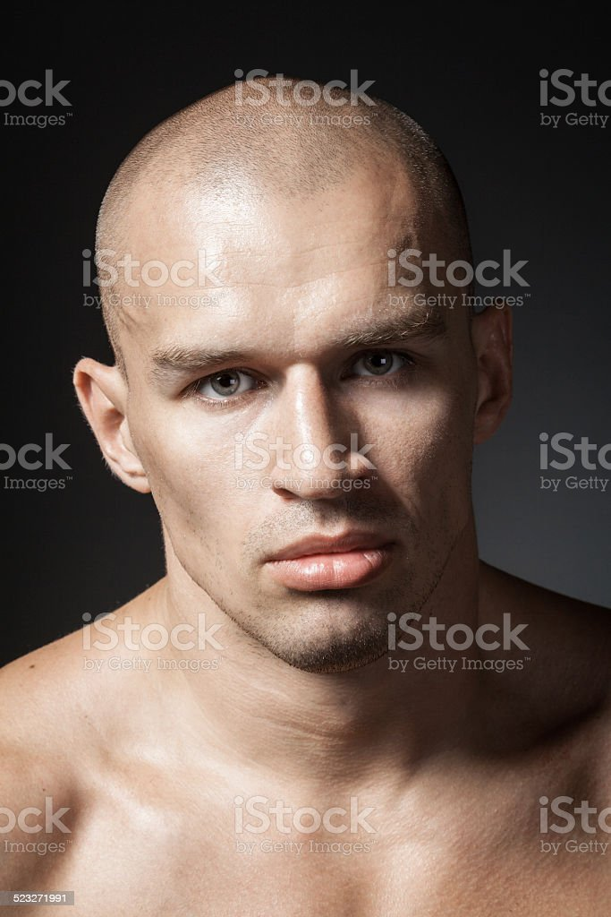 strong man portrait isolated on dark background stock photo