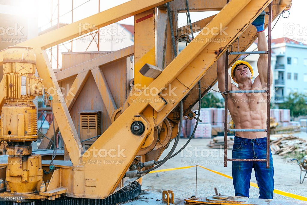 Strong manual worker climbing on construction crane stock photo