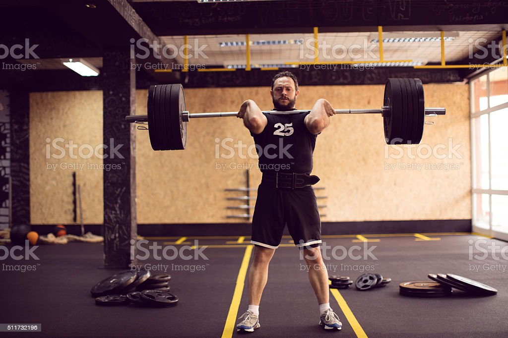 Strong mature aged man lifting big weight in the gym stock photo