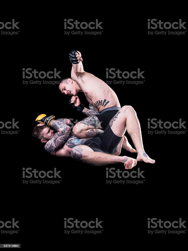 Strong MMA fighter holding his rival down and throwing punches stock photo