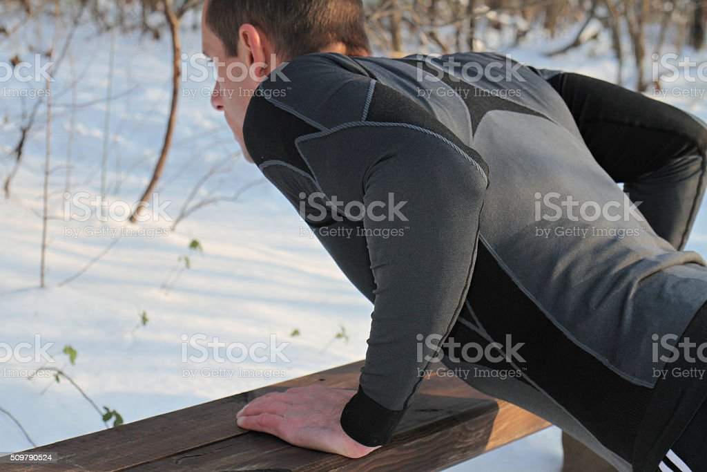 Strong muscular man push ups plank workout on  winter day. stock photo