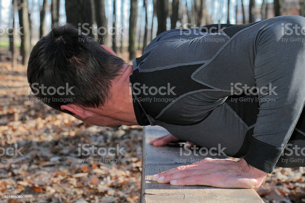 Strong muscular man push ups workout outdoor on cold day stock photo