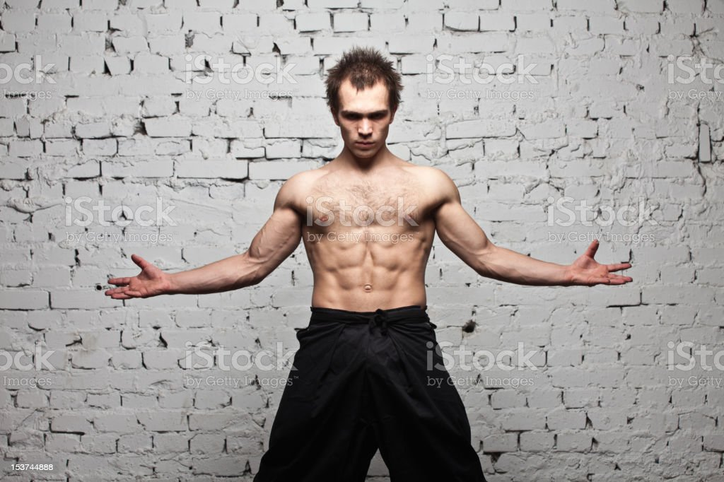 Strong muscular man stay at white brick wall royalty-free stock photo