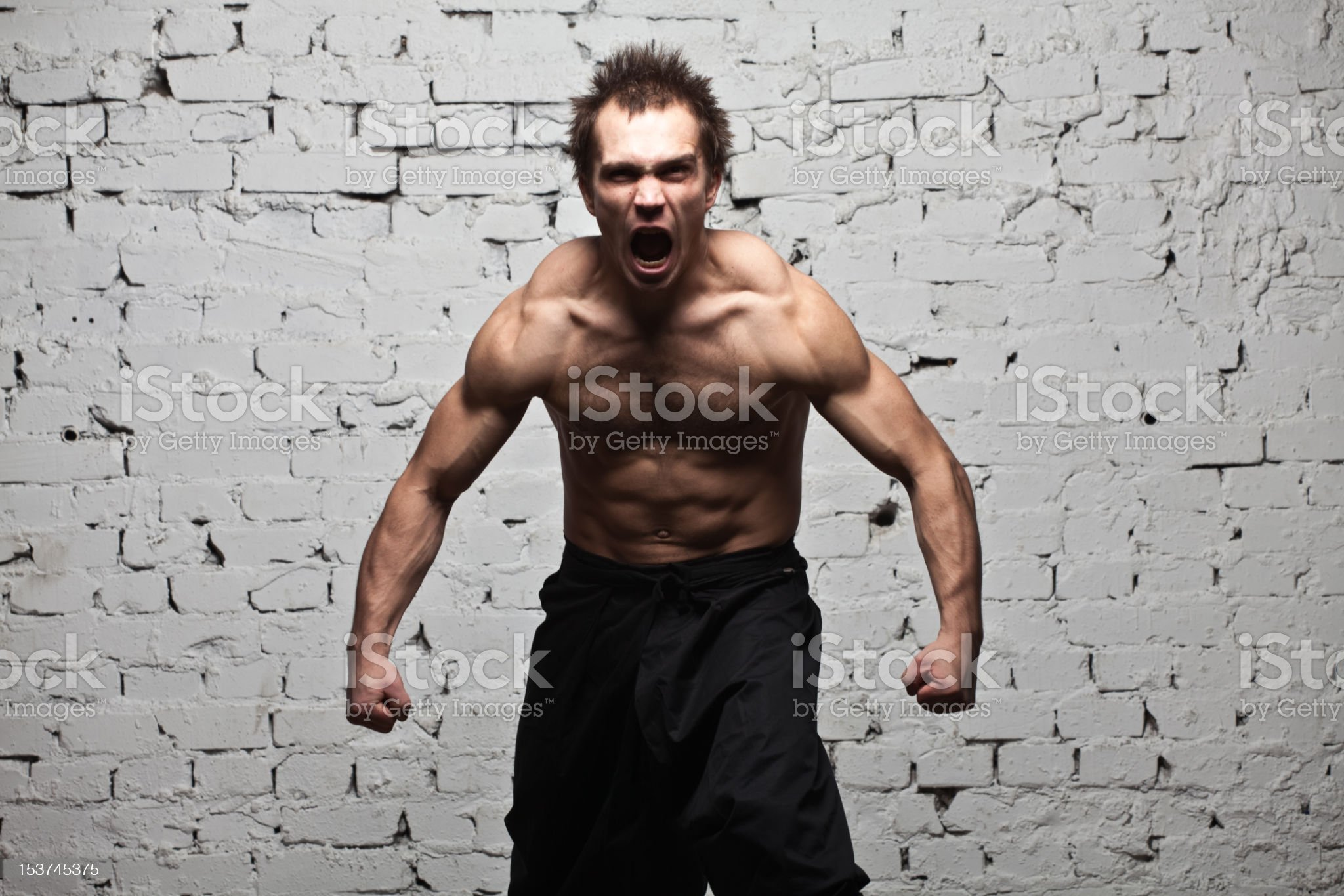 Strong muscular man stay in rage at white brick wall royalty-free stock photo