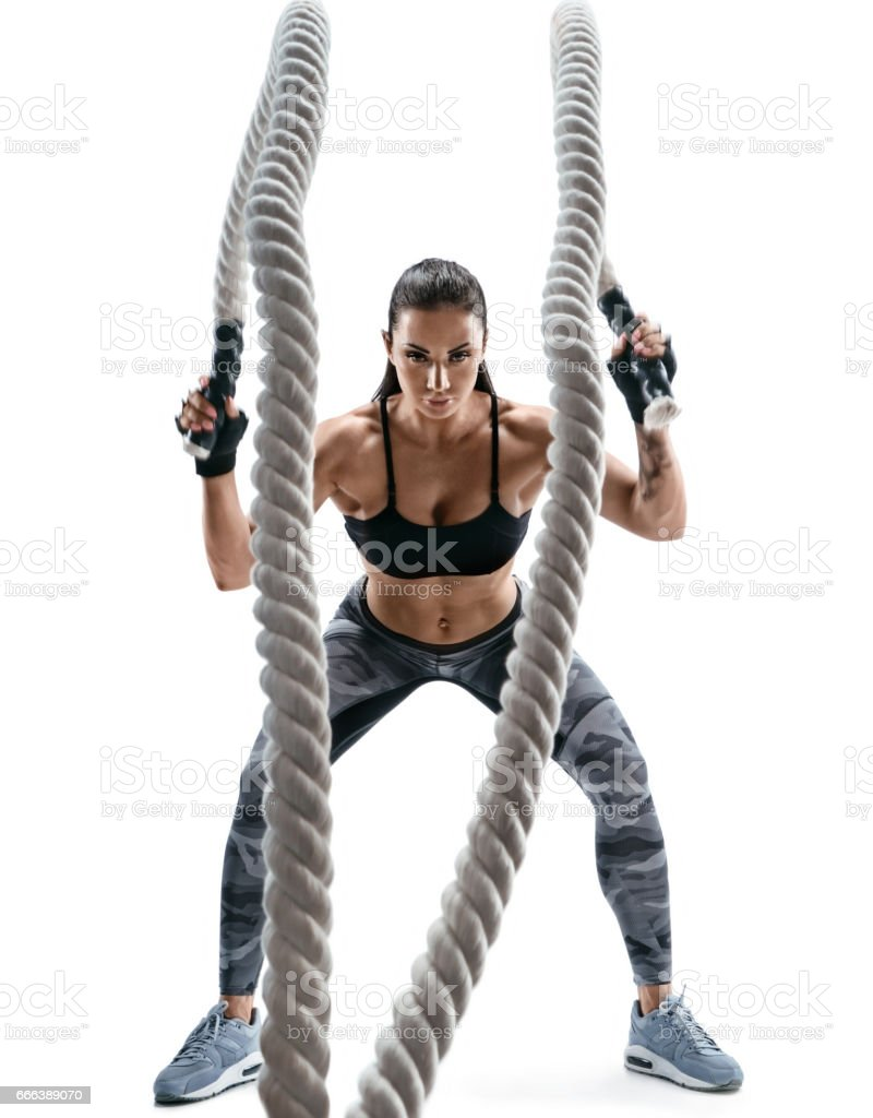 Strong muscular woman working out with heavy ropes stock photo